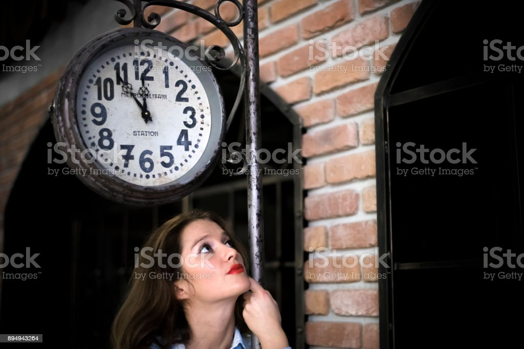 Young woman waiting for him - time concept. Old station background.