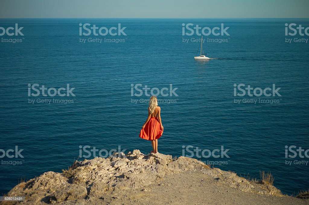 Young woman waiting for sailboat stock photo