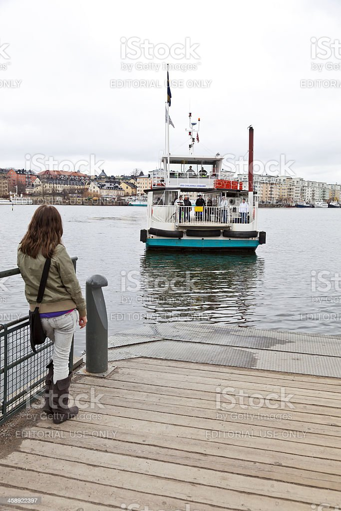 Young woman waiting for the ferry across Hammarby channel. royalty-free stock photo