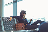 Shot of beautiful young woman waiting her flight at airport lounge using mobile phone