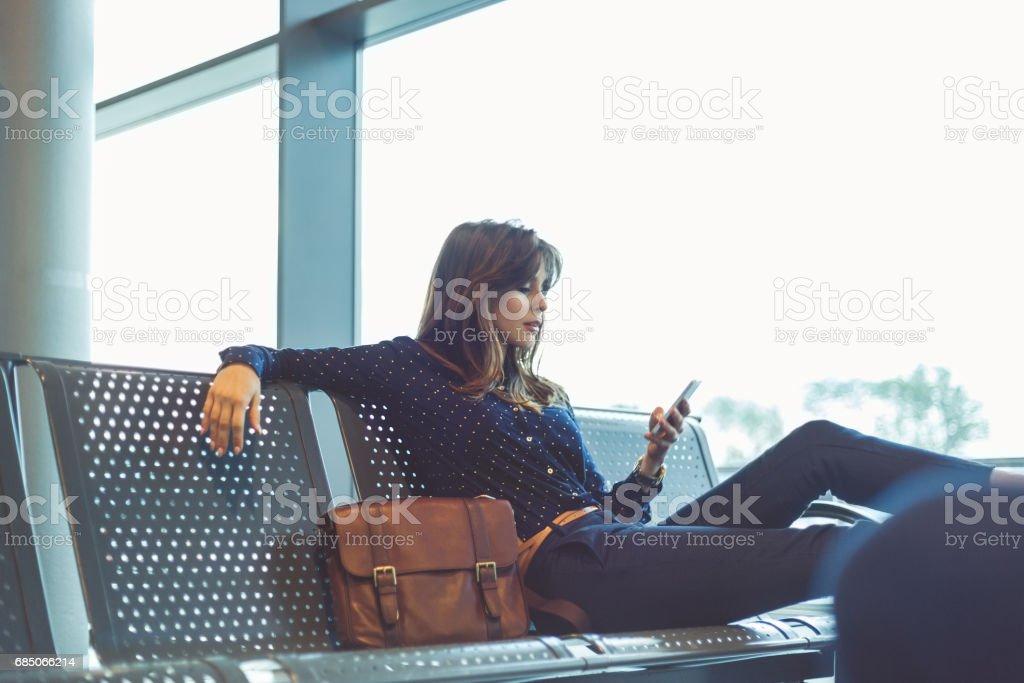 Junge Frau, die ihren Flug am Flughafen-Lounge warten – Foto