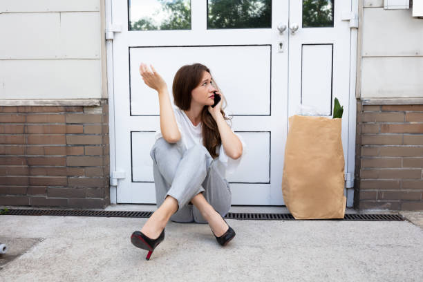 Young Woman Waiting In Front Of Closed Door An Afraid Young Woman Sitting Outside The Door Talking On Mobilephone locksmith stock pictures, royalty-free photos & images