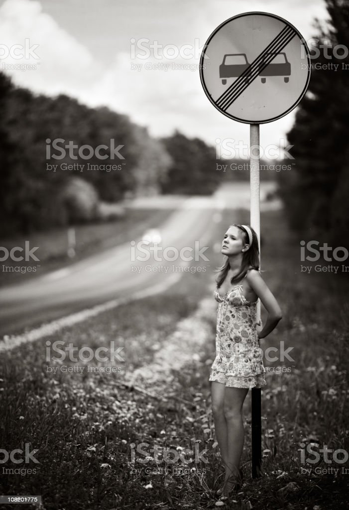 Young Woman Waits and Leans Against Roadside Traffic Sign royalty-free stock photo