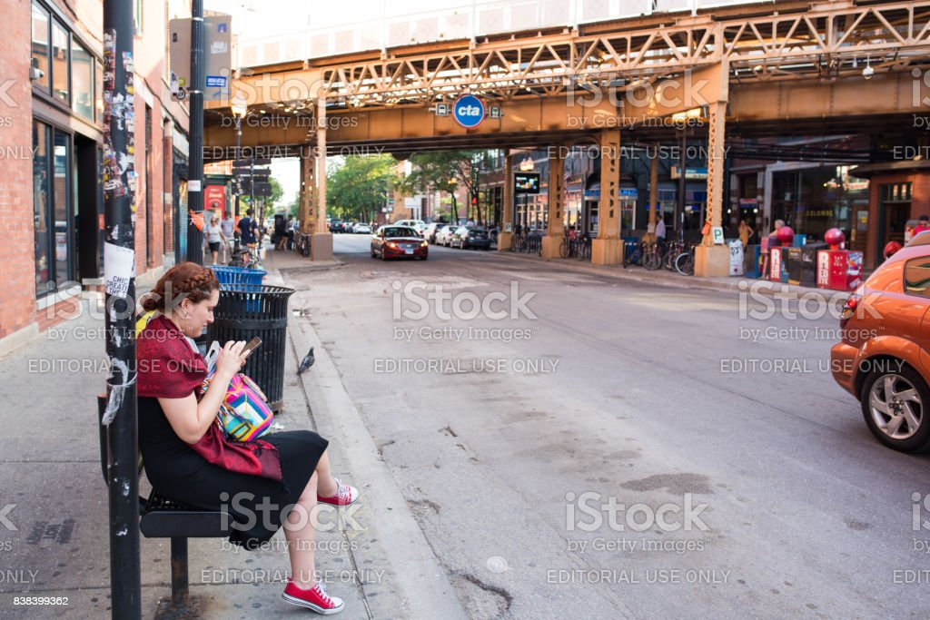Young woman waits for the bus in Wicker Park, Chicago stock photo
