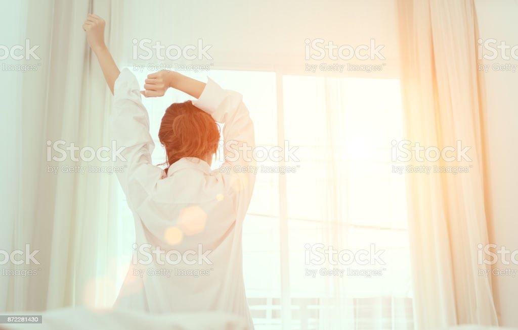 Genç kadın uyan sabah ve pencere kapı yan rahatlatıcı tatil ile güneş ışığı, geri, yatakta görünümü oturan - Royalty-free Aktif Hayat Tarzı Stok görsel