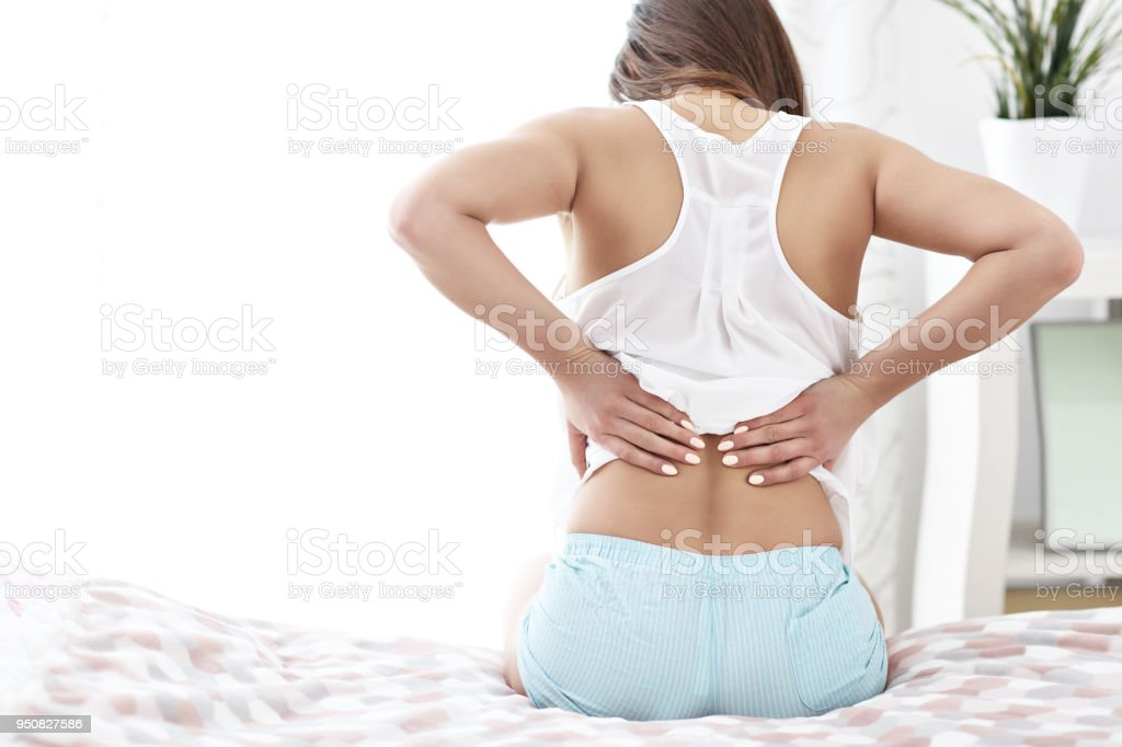 Young woman waking up in bed with backache stock photo