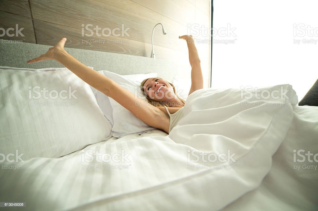Young woman waking up in her hotel room stock photo