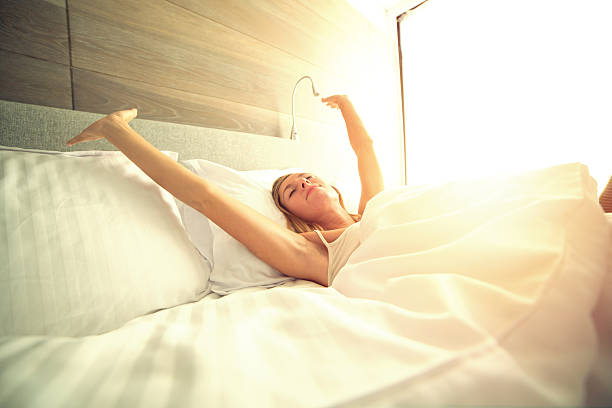 young woman waking up in her hotel room, stretching arms - hotelbett stock-fotos und bilder