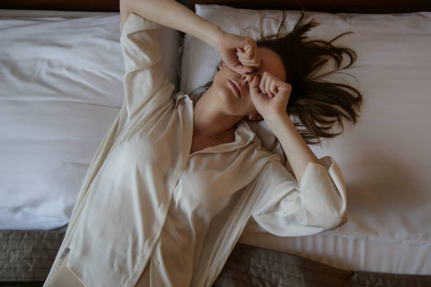 Young woman waking up, top view Young woman waking up, top view rubbing stock pictures, royalty-free photos & images