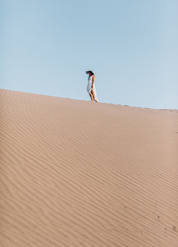 Rear view of young woman with white dress standing and walking on desert sand hill of Patara Beach against blue clear sky in Kaş, Kalkan, Antalya, Türkiye
