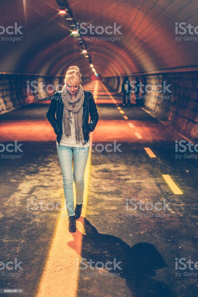 Young Woman walking Alone in the Tunnel stock photo