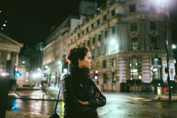 young woman walking alone on the streets of london at night - low lighting stock photos and pictures