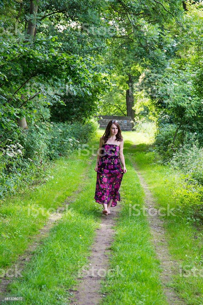 a15b01585 Joven mujer caminando por un sendero bosque. foto de stock libre de derechos