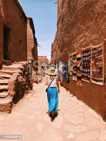 A young woman wearing a long blue skirt, white jersey and wicker hat is walking along a street in the Ait Ben Haddou village, hung with traditional Moroccan carpets. Blue cloudless sky on the background.