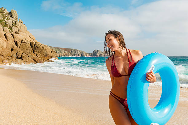 young woman walking along porthcurno beach on a bright day. - rubber ring stock pictures, royalty-free photos & images