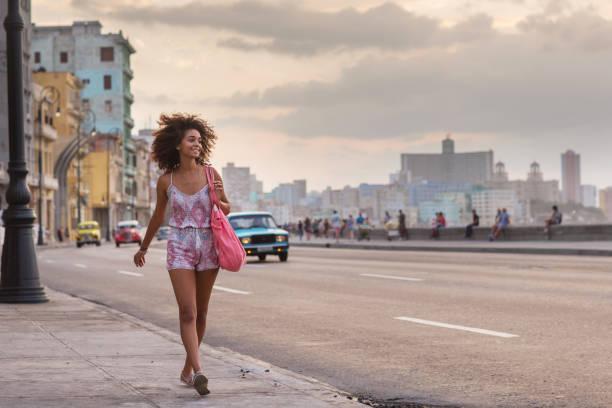 junge frau zu fuß entlang des malecon, havanna in der abenddämmerung - urlaub in kuba stock-fotos und bilder