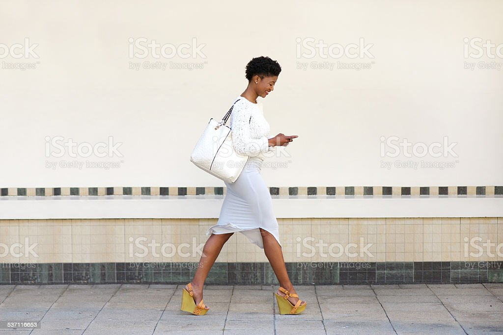 Young woman walking and sending text message on cell phone stock photo