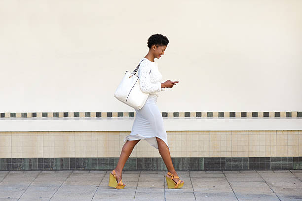 young woman walking and sending text message on cell phone - preppy fashion stock photos and pictures