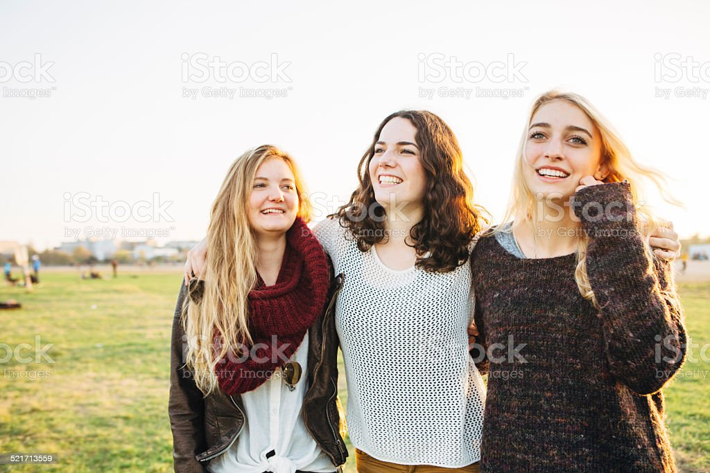 young woman walking arm in arm stock photo