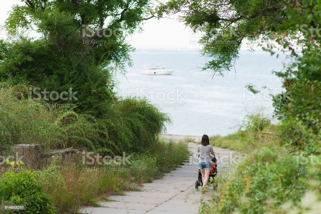 Young woman walking at sea background with little cute child baby boy in baby carriage on nature, green trees. Mother, little kid son. Parenthood, family day 15 of may, love, parents, children concept stock photo