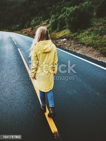 istock Young woman walking away on the road wearing yellow raincoat alone Travel Lifestyle emotions concept adventure vacations outdoor 1041757902