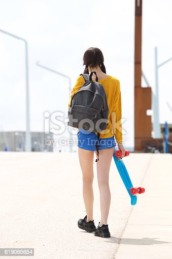 istock Young woman walking away with bag and skateboard 619065654