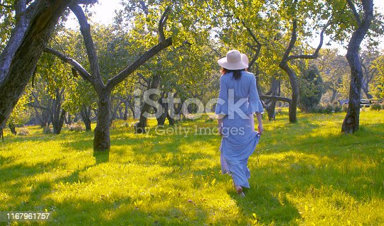 Young attractive woman in retro style dress walking barefoot on the grass of the garden
