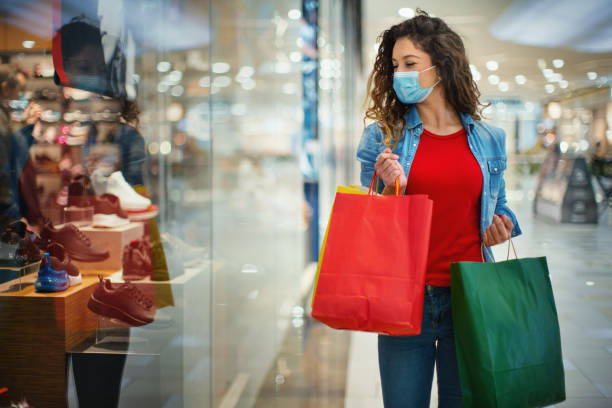 Young woman walking by store displays at shopping mall after reopening. stock photo