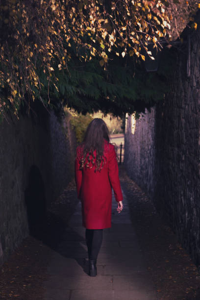 Young woman walking down a dark alley stock photo