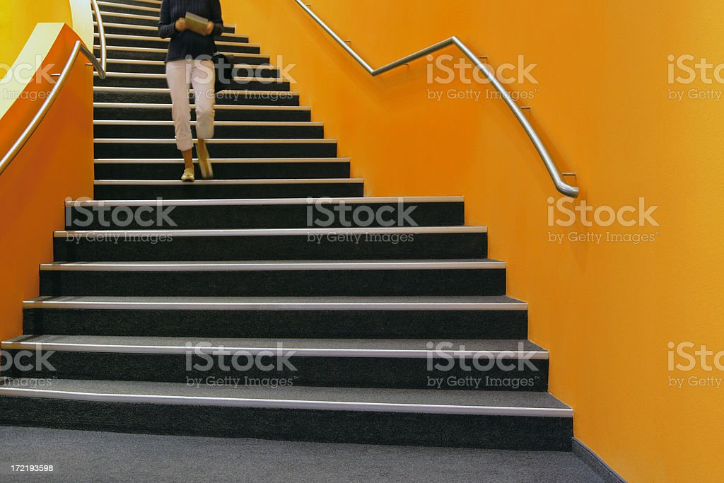 Young woman walking down orange stairs, reading book stock photo