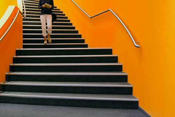 jeune femme marchant sur orange escaliers, livre - marches marches et escaliers photos et images de collection