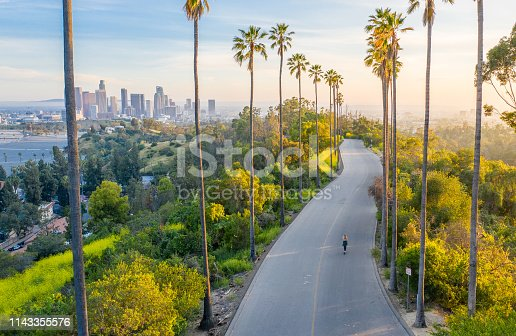 Drone shot of a woman walking down a street toward Downtown Los Angeles.