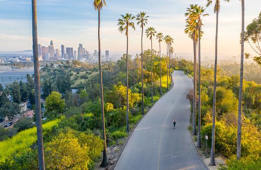 Drone shot of a woman walking down a street toward Downtown Los Angeles.