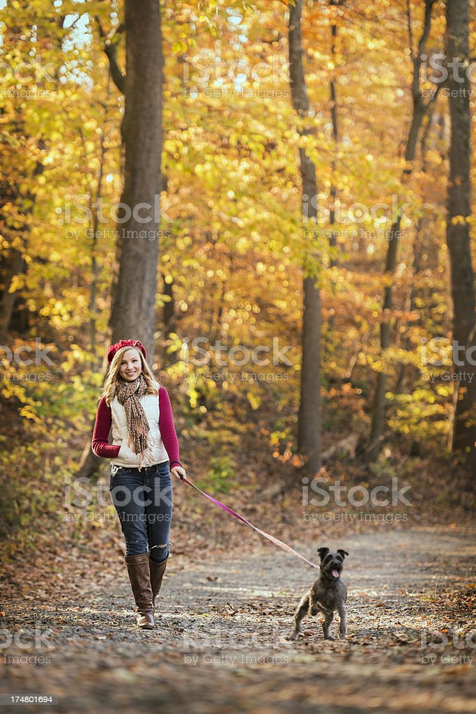 Young Woman Walking Her Dog on a Fall Day royalty-free stock photo