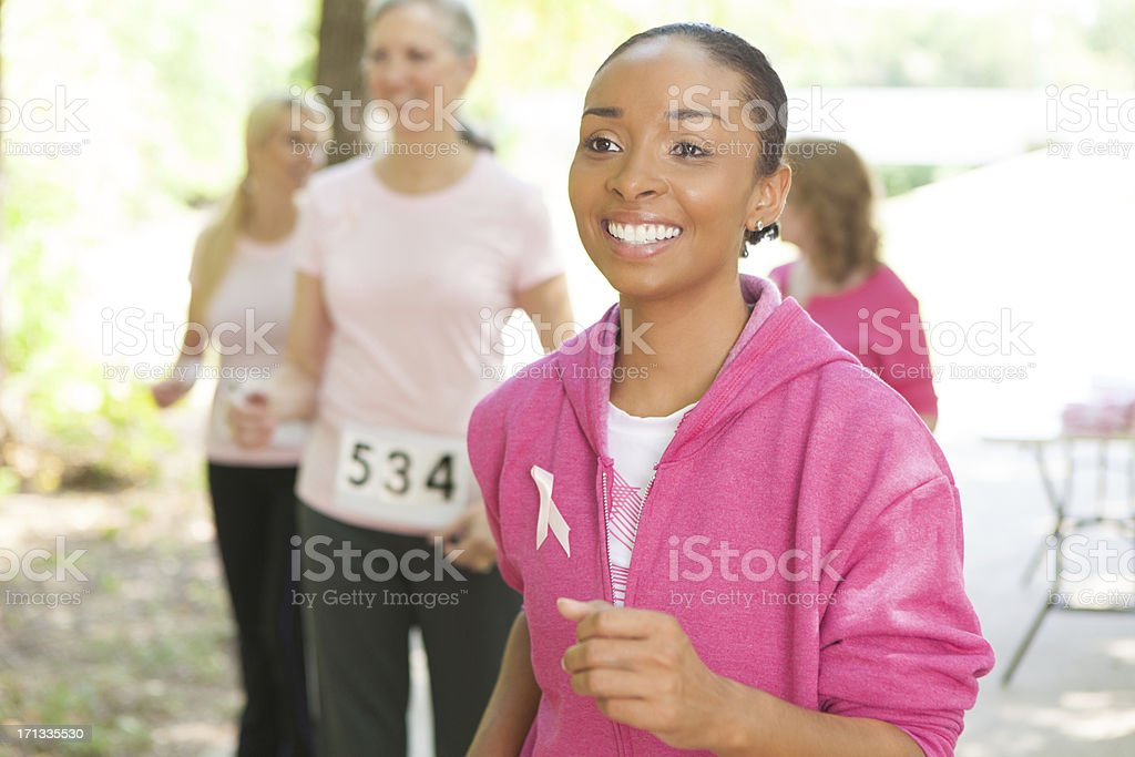 Young woman walking in a breast cancer awareness charity walk stock photo