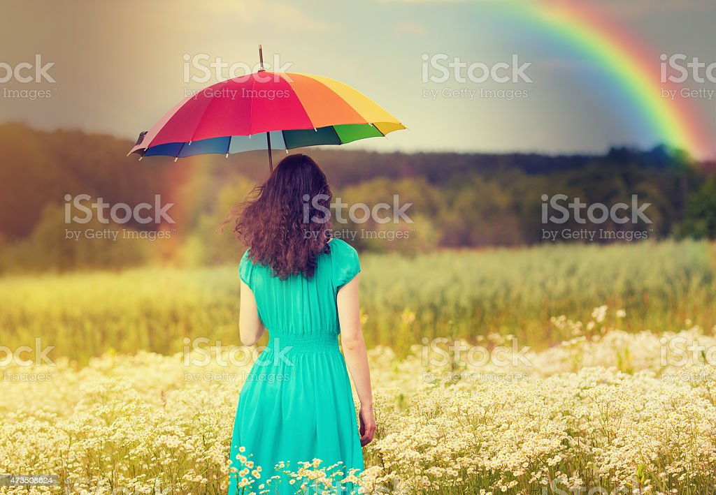 A young woman walking in a corn field underneath a rainbow stock photo