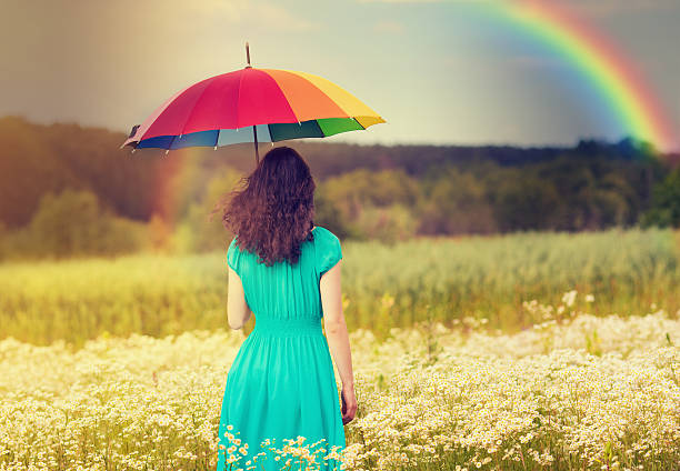 A young woman walking in a corn field underneath a rainbow Young woman walking on the field under umbrella in fair weather sun shining through dresses stock pictures, royalty-free photos & images