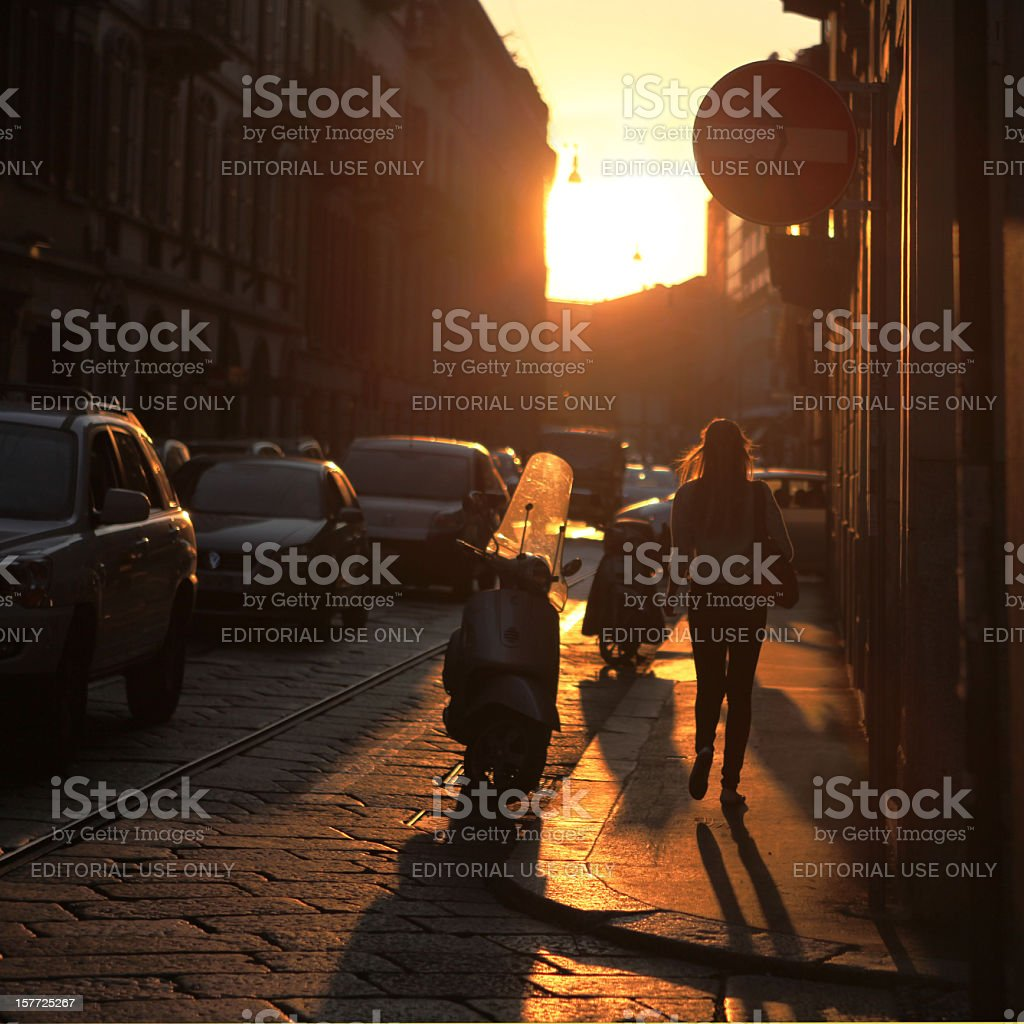 Young woman walking in a street at sunset, Milan, Italy royalty-free stock photo