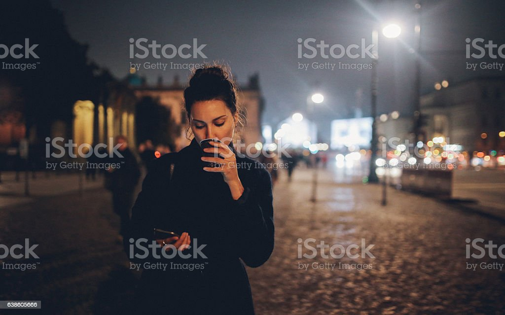 Young woman walking in Berlin at night checking phone stock photo