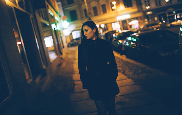 young woman walking in berlin mitte - low lighting stock photos and pictures