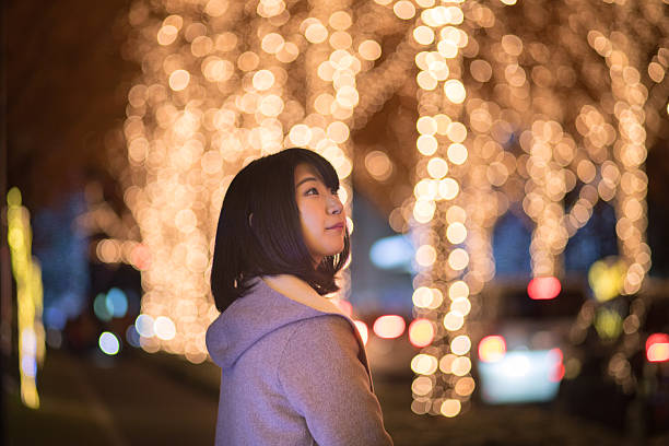 young woman walking in christmas lights - weihnachten japan stock-fotos und bilder