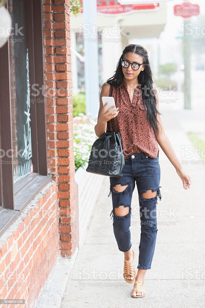 Young woman walking in city looking at mobile phone stock photo