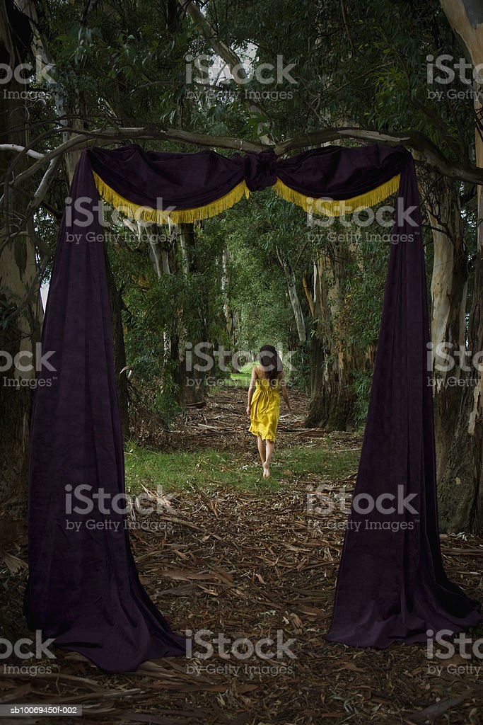 Young woman walking in forest with door made up of curtain royalty-free stock photo