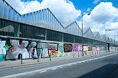 Paris-France, April, 25 2018; Young woman walking in front of colorful graffiti in Paris