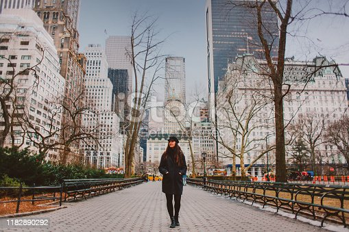 Young woman wearing a hat and a dark coat, walking through the Central Park in NYC. She is sightseeing or just getting back home from work.