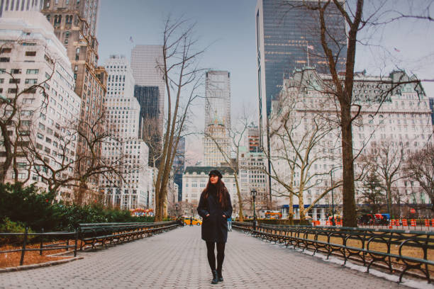 Young woman walking in NYC Central park in winter stock photo