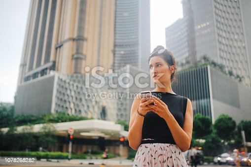 Young brunette woman traveling alone in Singapore. She is checking the online maps for navigation, looking where to go next, walk or maybe call a taxi.