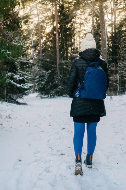 Young woman walking in snowy forest - foto de stock