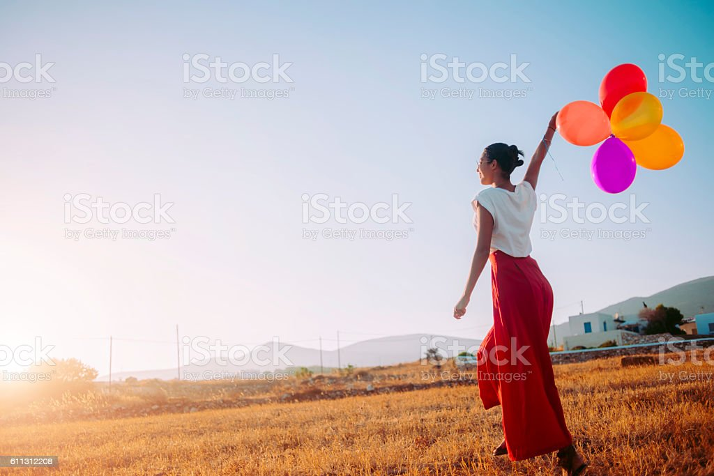 young woman walking in the field holding colorful balloons stock photo