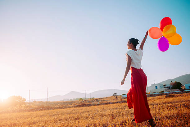 young woman walking in the field holding colorful balloons young woman walking in the field holding colorful balloons,nice warm light and sunbeam,blue sky in the background sun shining through dresses stock pictures, royalty-free photos & images